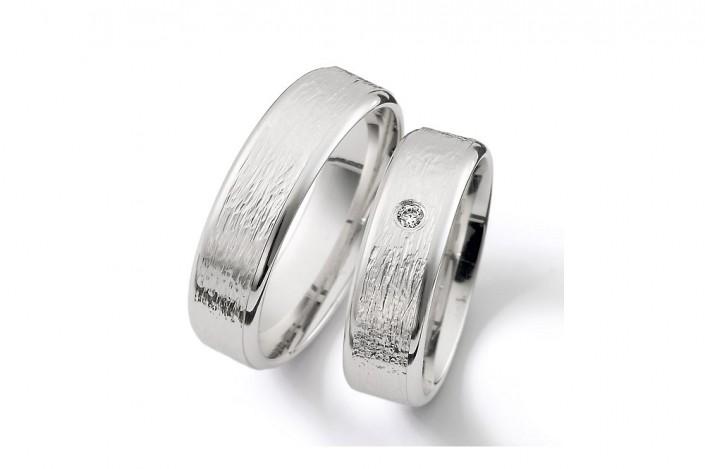 Vielsesringe i børstet og råt look med en enkelt diamant i brilliantslibning i smuk indfatning centralt på ringskinnen.