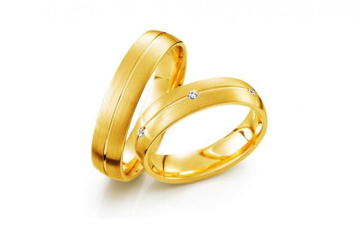 Vielsesringe i guld med enkle diamanter i et smukt bånd, slebet i en smuk brilliantslibning.