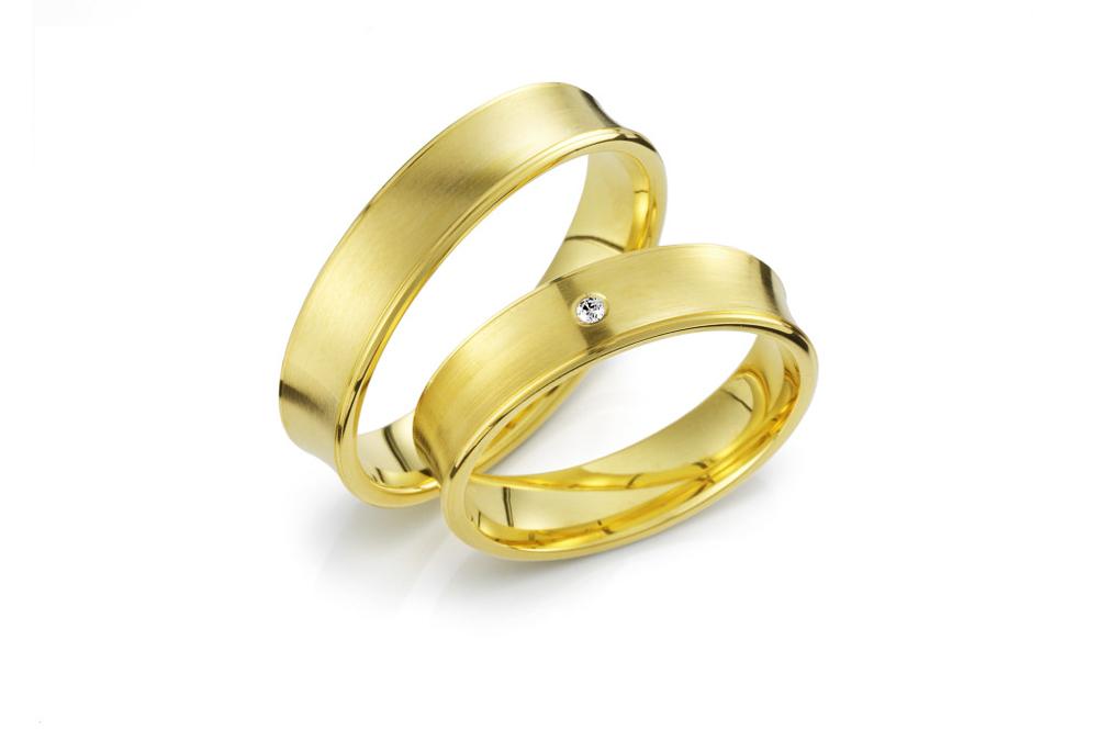 Vielsesringe i guld med en indadkurvet ringskinne med brilliantslebet diamant placeret i midten.