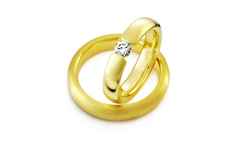 Vielsesringe i guld med et unikt look der har en smuk diamant der bryder ringskinnen midtpå.